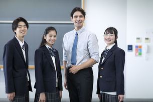 外国人教師と並んで笑顔の高校生の写真素材 [FYI04793134]