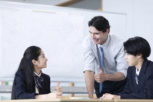 外国人教師と話す高校生の写真素材 [FYI04793137]