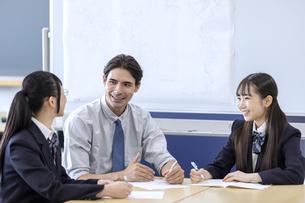 外国人教師と話す高校生の写真素材 [FYI04793139]