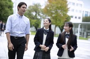 外国人と会話しながら歩く高校生の写真素材 [FYI04793156]
