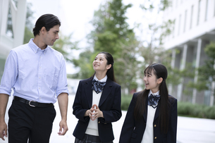 外国人と会話しながら歩く高校生の写真素材 [FYI04793157]
