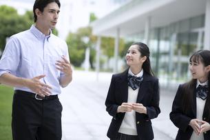 外国人と会話しながら歩く高校生の写真素材 [FYI04793158]