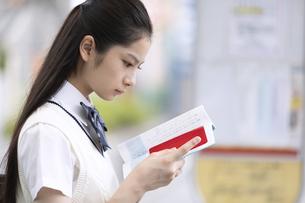 勉強しながらバスを待つ女子高校生の写真素材 [FYI04793168]