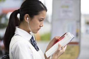 勉強しながらバスを待つ女子高校生の写真素材 [FYI04793172]