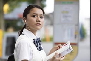 勉強しながらバスを待つ女子高校生の写真素材 [FYI04793173]