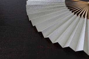 漆塗り板背景の銀色の扇子の写真素材 [FYI04794246]