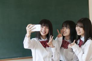 教室でスマホで写真を撮る女子学生の写真素材 [FYI04794448]