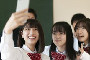 教室でスマホで写真を撮る学生の写真素材 [FYI04794452]