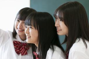 教室で寄り添う女子学生の写真素材 [FYI04794454]