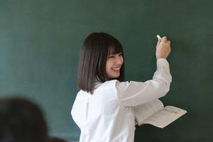 教室で黒板に向かう女子学生の写真素材 [FYI04794457]