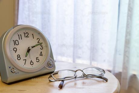 窓際の置き時計とめがねの写真素材 [FYI04794681]