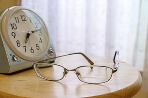 窓際に置かれた時計と眼鏡の写真素材 [FYI04794682]