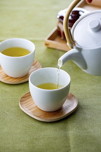 Cups of green tea and teapot. Pouring fresh green tea in the cups.の写真素材 [FYI04794917]