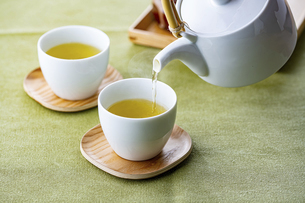 Cups of green tea and teapot. Pouring fresh green tea in the cups.の写真素材 [FYI04794919]