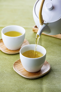 Cups of green tea and teapot. Pouring fresh green tea in the cups.の写真素材 [FYI04794921]