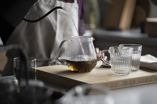 Woman is making hot tea in the kitchen.の写真素材 [FYI04794926]