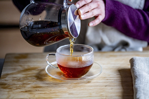 Woman is making hot tea in the kitchen.の写真素材 [FYI04794935]