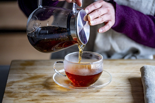 Woman is making hot tea in the kitchen.の写真素材 [FYI04794936]