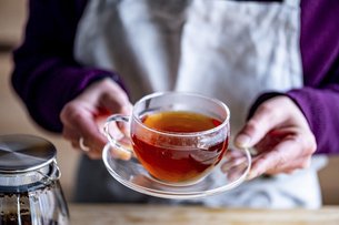 Woman holding a cup of hot black tea.の写真素材 [FYI04794938]