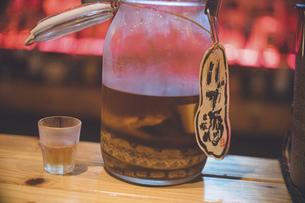 ハブ(毒ヘビ)の入ったハブ酒のボトルとグラス 沖縄那覇のバーの写真素材 [FYI04795155]
