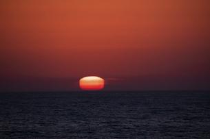 蜃気楼で四角く変形して沈む太陽の写真素材 [FYI04795168]