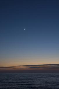 静かな海の夕暮れと三日月と金星の写真素材 [FYI04795185]