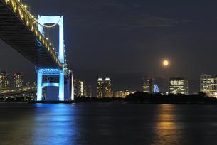 満月と青色にライトアップされたレインボーブリッジの写真素材 [FYI04795551]