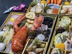 テーブルに広げた3段重ねのお節料理の写真素材 [FYI04795628]