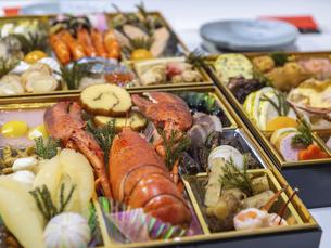 テーブルに広げた3段重ねのお節料理の写真素材 [FYI04795631]