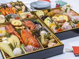 テーブルに広げた3段重ねのお節料理の写真素材 [FYI04795635]