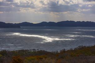 雲間から差す日差しに光る津軽の荒れた海の写真素材 [FYI04795852]