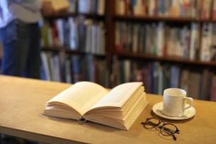 デスクに置かれた本とコーヒーとメガネの写真素材 [FYI04796366]