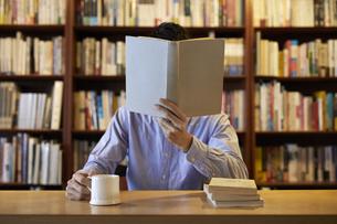 顔の前で本を開く男性の写真素材 [FYI04796367]