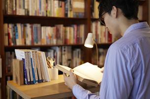 デスクで本を読む男性の写真素材 [FYI04796369]