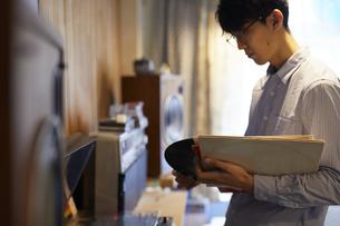 レコードプレイヤーの前に立ってレコードを選ぶ男性の写真素材 [FYI04796373]