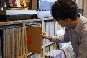 棚からレコードを引き出す男性の写真素材 [FYI04796374]