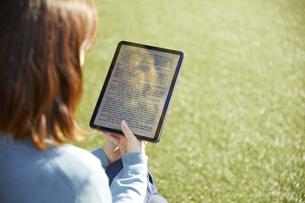 人工芝の広場でタブレットを使って電子書籍を読む女性の写真素材 [FYI04796375]