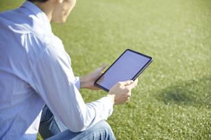 人工芝の広場でタブレットを使って電子書籍を読む男性の写真素材 [FYI04796376]
