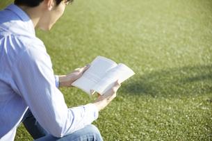 人工芝の広場で本を読む男性の写真素材 [FYI04796377]