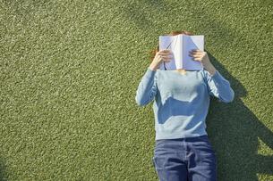 人工芝に寝転んで本を読む女性の写真素材 [FYI04796379]