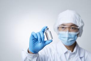 ワクチンを見つめる白衣を着た男性の写真素材 [FYI04796396]