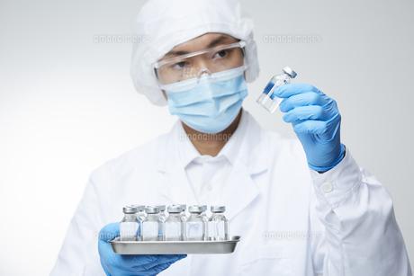 沢山の瓶の中から一つ選ぶ白衣を着た男性の写真素材 [FYI04796404]
