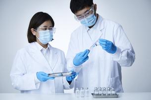注射器を瓶に差し込む白衣を着た男性と女性の写真素材 [FYI04796425]