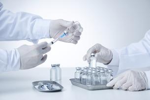 白衣を着てワクチンを触る研究者2人の手元の写真素材 [FYI04796433]