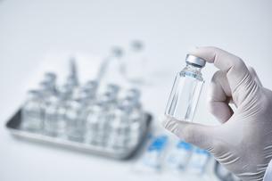 ワクチンの瓶を1つ持つ研究者の手の写真素材 [FYI04796434]
