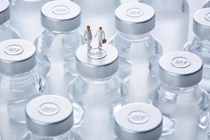 バイアル瓶の上に乗っているミニチュアの医療従事者の写真素材 [FYI04796459]