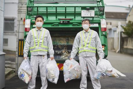 パッカー車とゴミ収集をする男性の作業員の写真素材 [FYI04796469]