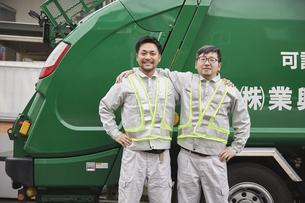 パッカー車と肩を組む男性の作業員の写真素材 [FYI04796477]