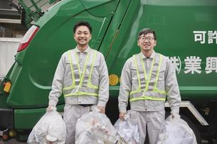 パッカー車とゴミを持つ男性の作業員の写真素材 [FYI04796478]