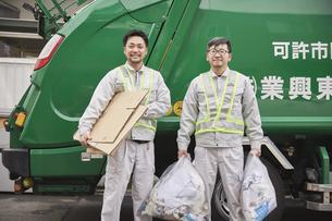 パッカー車とゴミを持つ男性の作業員の写真素材 [FYI04796479]